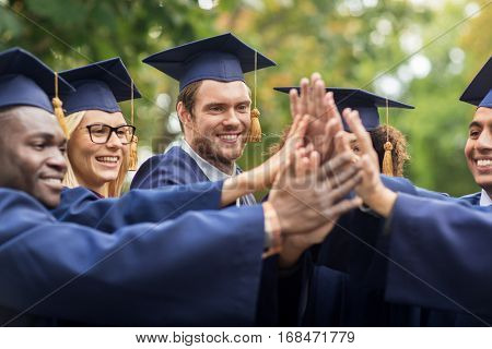 education, graduation and people concept - group of happy international students in mortar boards and bachelor gowns making high five