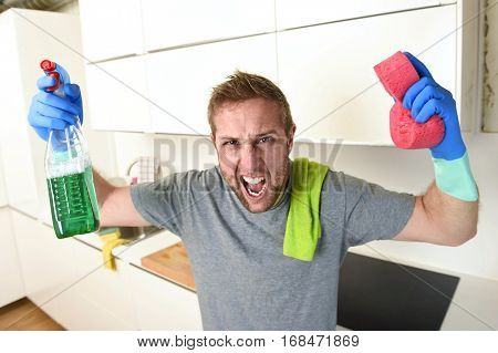 young man holding cleaning detergent spray and sponge washing and making home kitchen clean screaming desperate in stress and frustration tired and exhausted in husband domestic wash concept