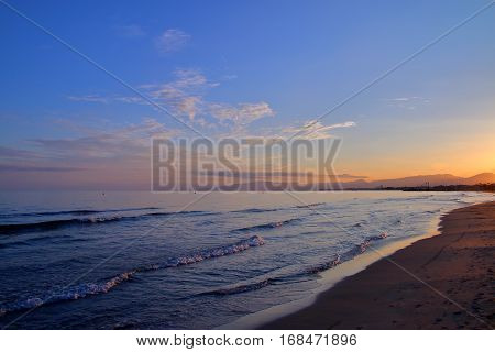 The picture was taken in Spain Salou. The picture shows a beach on the Mediterranean sea lit by the setting sun.