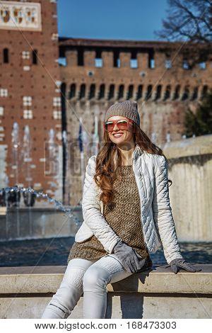 Woman In Front Of Sforza Castle In Milan Sitting Near Fountain