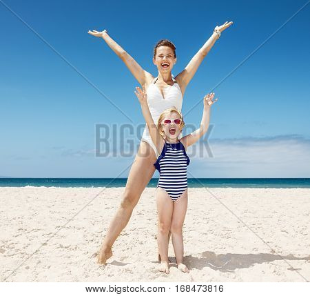 Happy Mother And Child In Swimsuits At Sandy Beach Rejoicing