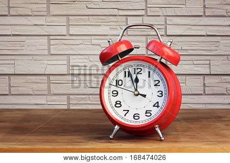 Red retro alarm clock at twelve o'clock on brick wall background. Midnight midday.