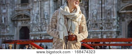 Rediscovering things everybody love in Milan. happy young traveller woman in fur coat in Milan Italy looking into the distance