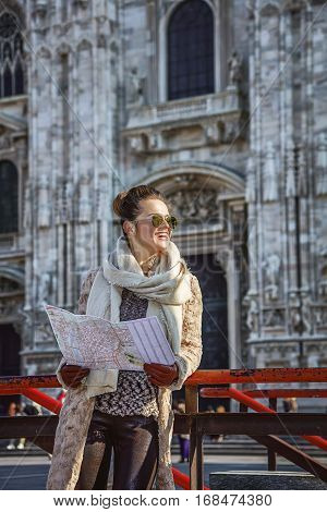Rediscovering things everybody love in Milan. smiling young woman in fur coat and sunglasses in Milan Italy with map looking into the distance