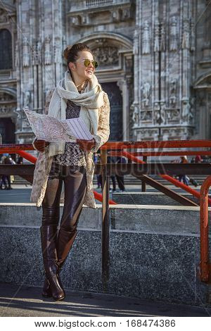 Tourist Woman In Milan, Italy With Map Looking Into Distance