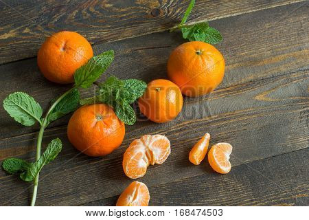 Several mandarin oranges on a wooden background with mint