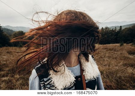 Beautiful Hipster Traveler Having Fun In Windy Mountains, Playing With Hair. Stylish Woman Hiking. W