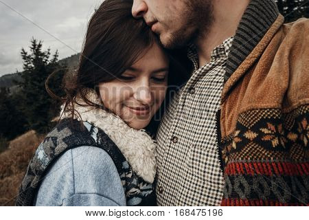 Happy Hipster Traveler Couple Hugging On Top Of Mountains. Romantic Moment Of Stylish Family. Wander