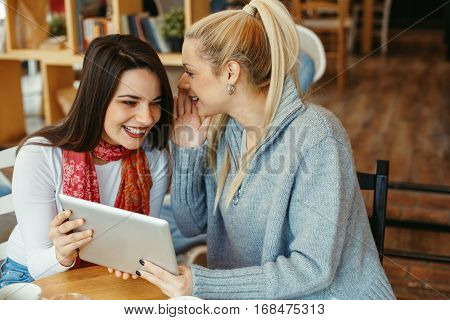 Two young women in a cafe have fun with tablet and gossiping