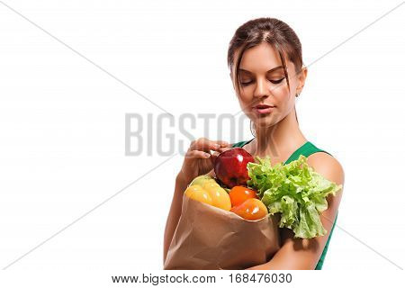 A girl holding a bag of fruits and vegetables paper bag with organic fresh food isolated on white background. . Girl holding bag with vegetables and fruits and looks at red apple in his hand.