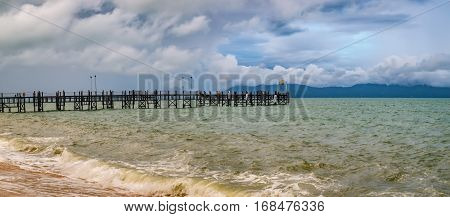 Old wooden pier stretching out to sea and foamy waves on the Maenam Beach, Koh Samui, Thailand. Rainy ominous grey storm clouds - dramatic sky