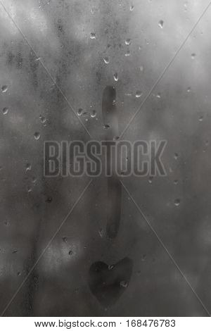 The exclamation point with a point-heart on the glass with rain drops on a gray sky background