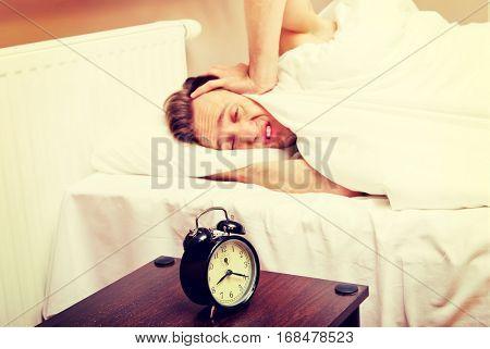 Man trying to sleep, when alarm clock ringing