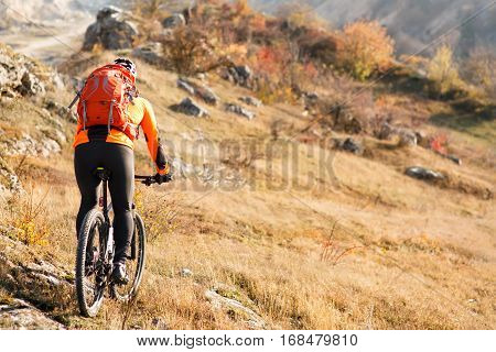 cyclist-traveler with a backpack on mountain bike rides on a mountain trail in spring season. countryside. beautiful landscape. cyclist in white helmet with red backpack. back view.