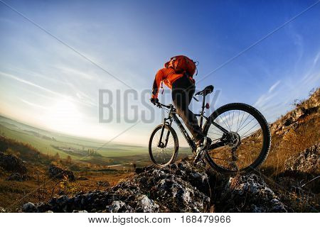 back view of a man with a bicycle and red backpack against the blue sky. cyclist rides a bicycle. Rear view people collection. backside view of person. blue sky background and mound.