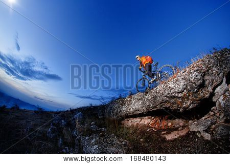 Cyclist Riding the Bike Down Hill on the Mountain Rocky Trail at Sunset. Extreme Sports. Durknest time. Evening time. beautiful landskape. fisheye.
