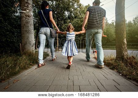Happy Stylish Parents Holding Hands With Daughter And Walking In Sunny Summer Street, Tender Family