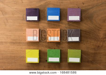 Index, menu or cover abstract back ground, with blank white space for custom text, consisting of nine hand painted colored wooden cubes on grungy wooden background with vintage taste.
