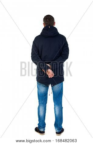 Back view of handsome man in winter jacket  looking up. Standing young guy in parka. Rear view people collection. backside view of person. Man in warm jacket put his hands behind his back and standing