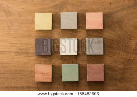 Index, menu or cover abstract back ground, consisting of nine hand painted colored wooden cubes on grungy wooden background with vintage taste.  Earth tone. beige, brown, creme, amber, khaki.