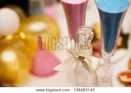 Sand ceremony on wedding glass vase for bride and groom. Marriage concept. Pink and blue
