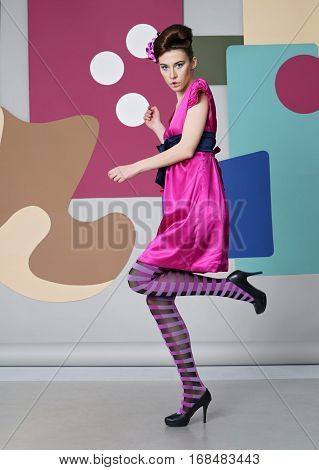 Color composition. Eccentric outfit. Short dress, high heels, striped tights. Simple shapes - circles, rectangles.