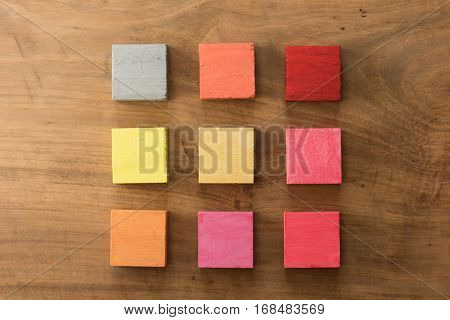 Index, menu or cover abstract back ground, consisting of nine hand painted colored wooden cubes on grungy wooden background with vintage taste.   orange, yellow, gray, red, pink, magenta.