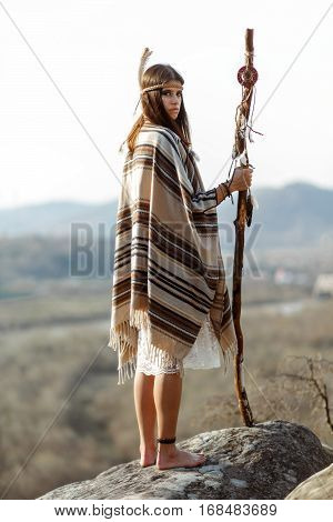 Beautiful Native Indian American Woman With Warrior Shaman Make Up Standing On Rocks On Background O