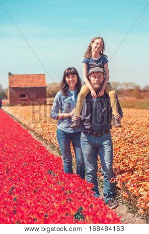 Happy loving family with a kid in a Dutch tulips field