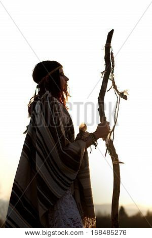 Silhouette Of Native Indian American Woman Shaman On Hill  In Sunset Evening Mountains
