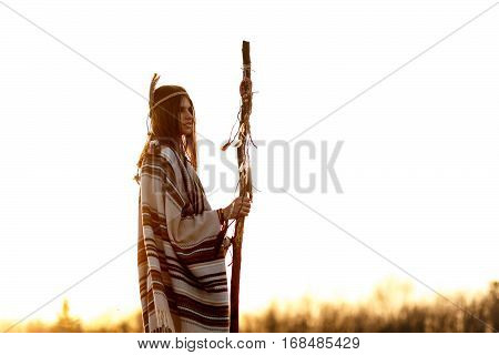 Native American Woman  Shaman With Pikestaff On Background Of Sunset Beutiful In Mountains
