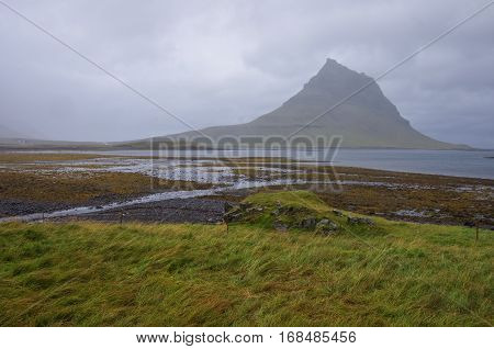 Kirkjufell Mountain Into Clouds. Snaefellsnes Peninsula With Fall Of Tide In Atlantic Ocean, Iceland