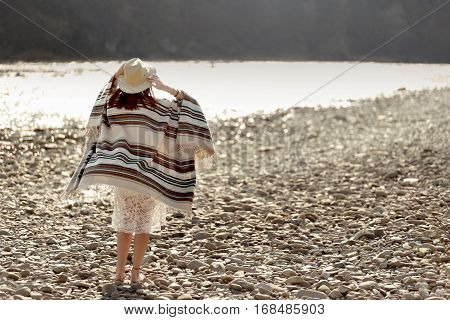 Beautiful Woman Traveler Wearing Hat And Poncho Walking At River Beach, American Outfit, Boho Concep