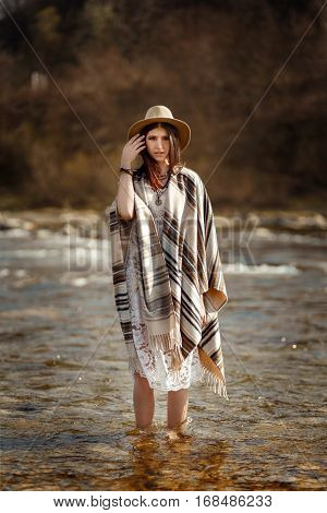 Beautiful Woman Traveler Wearing Hat And Poncho Standing In Water Of River, Stylish Outfit, Boho Tra