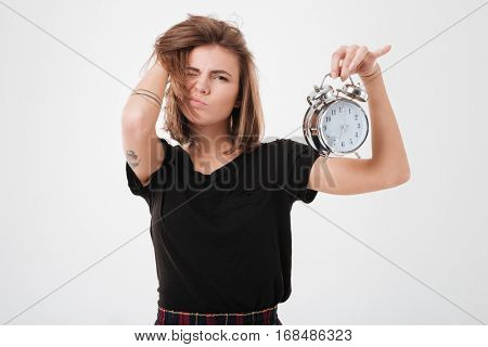 Portrait of a tired unsatisfied girl with messy hair holding alarm clock over white background