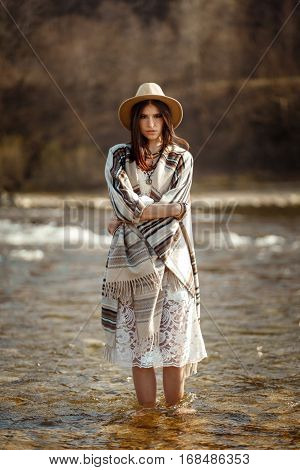 Beautiful Woman Hipster Wearing Hat And Poncho Standing In Water Of River, Stylish Outfit, Boho Trav