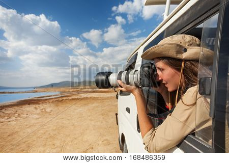 Close-up picture of young woman taking photo of Kenyan lake from the open window of safari jeep