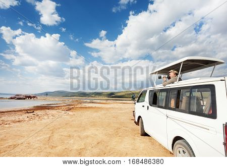 Professional photographer making shoot of hippopotamus from minibus at Kenyan savannah, Africa