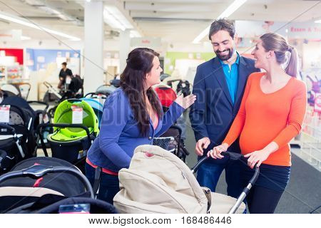 Woman, man, and sales lady in baby store testing buggy
