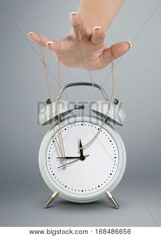 Hand puppeteer manipulating alarm clock time management concept