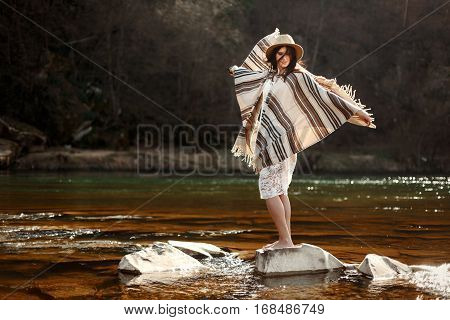 Beautiful Woman Traveler Standing On Rocks In River And Playing With Wind, Wearing Hat And Poncho, B