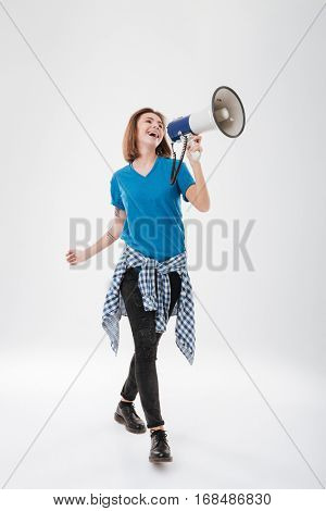 Full length portrait of a happy casual girl walking and yelling in megaphone isolated on a white background