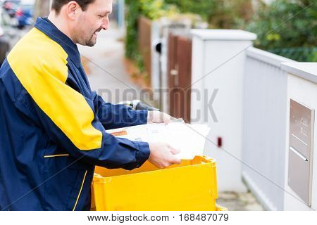 Postman delivering letters to mailbox of recipient