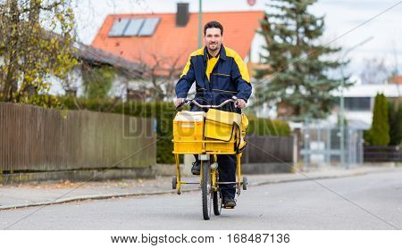 Postman riding his cargo bike carrying out mail in neighborhood