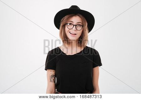 Portrait of a confused young girl in hat making funny face and looking at camera isolated on a white background