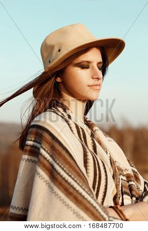 Beautiful Woman Hipster Portrait, With Romantic Look, Wearing Hat And Poncho At Sunset In Mountains,