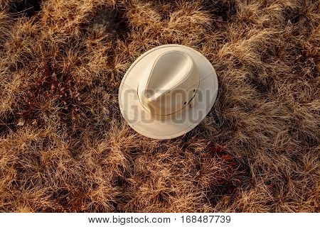 old boho or cowboy hat on grass at sunset in mountains travel concept space for text