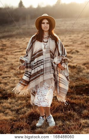 Beautiful Woman Hipster Posing, Wearing Hat And Poncho,  At Sunset In Mountains
