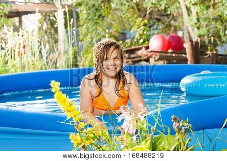 Portrait of smiling ten years old girl posing in the blue inflatable pool in summer