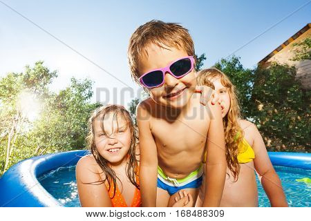 Close-up portrait of smiling boy and two girls having fun in the blue swimming pool outside at sunny day